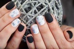 De handen met manicured spijkers met zwart-wit nagellak worden gekleurd dat Stock Foto