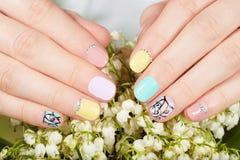 De handen met mooi manicured spijkers en lelietje-van-dalenbloemen Royalty-vrije Stock Afbeelding