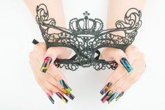 De handen met mooie manicure die een zwart kant Carnaval houden maskeren op witte achtergrond royalty-vrije stock foto