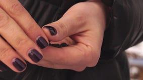 De handen met zwarte spijkers maken zonnebloemzaden van shell schoon stock footage