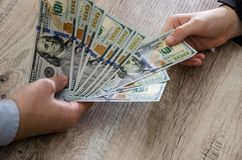 De handen nemen en geven dollarsbankbiljetten stock fotografie