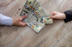 De handen nemen en geven dollarsbankbiljetten stock foto's