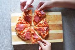 De handen nemen plakken van pizza stock afbeelding