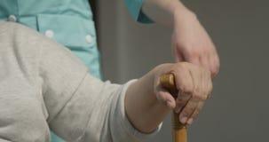 De handen op Wandelstokverpleegster Putting haar Palm op Oude Dame Concept van Zorg voor Bejaarden en van Liefde Dicht omhooggaan stock videobeelden