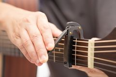 De handen passen capo aan om het geluid van guit aan te passen stock foto