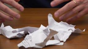De handen roeien weg gescheurde documenten en tonen vuisten met een koekje stock video