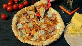 De handen snijden onhandig pizza, op plakken, met worst, tomaat en kaas, met speciaal mes af - snijderswiel Op houten stock footage
