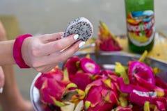 De handen snijden pitohaya op een plaat Stock Foto