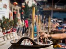 De handen steken Wierookstokken bij joss stokpot het branden en rook neer wordt gebruikt om eerbied aan Boedha te betalen die stock foto