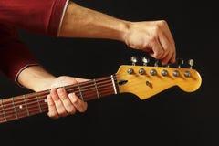De handen stemt de gitaar op zwarte achtergrond royalty-vrije stock afbeeldingen