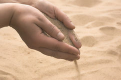 De handen strooien zand uit Royalty-vrije Stock Fotografie