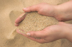 De handen strooien zand uit Stock Foto's