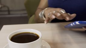 De handen van Afrikaanse vrouw die het scherm van tablet in de koffie scrollen, sluiten omhoog stock video
