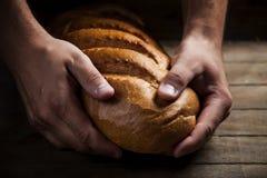 De handen van Baker met een brood Stock Afbeelding