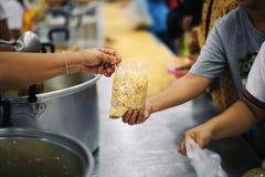 De handen van bedelaars ontvangen geschonken voedsel als aandeel in de maatschappij: het concept honger stock afbeeldingen
