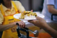 De handen van bedelaars ontvangen geschonken voedsel als aandeel in de maatschappij: het concept honger royalty-vrije stock foto