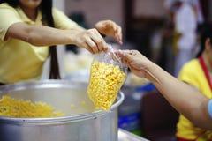 De handen van bedelaars ontvangen geschonken voedsel als aandeel in de maatschappij: het concept honger stock foto
