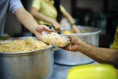 De handen van bedelaars ontvangen geschonken voedsel als aandeel in de maatschappij: het concept honger royalty-vrije stock fotografie