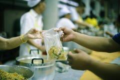 De handen van bedelaars ontvangen geschonken voedsel als aandeel in de maatschappij: het concept honger stock afbeelding