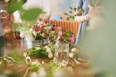 de handen van bloemist verzamelen huwelijksboeket op het werk royalty-vrije stock afbeeldingen