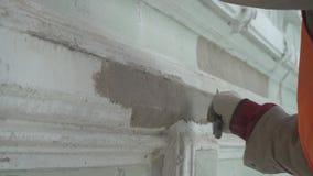 De handen van de bouwvakker pleisteren regelmatig grijze muur met groot spacklemes stock footage