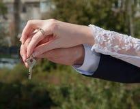 De handen van bruid en bruidegom houden de sleutel Stock Foto