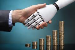 De Handen van Businesspersonand robot shaking stock afbeelding