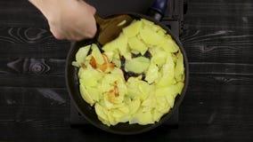 De handen van de chef-kok van het wijfje keren gesneden aardappelachtige spaanders om die in een pan tot gouden bruin braden De o stock videobeelden