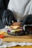 De handen van chef-kok koken de Hamburger Het concept het koken van zwarte cheeseburger Eigengemaakt hamburgerrecept stock foto