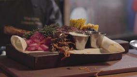 De handen van chef-kok in zwarte kok gloves het verfraaien met tak van kruid geroosterd vlees liggend op pitabroodje met rode koo stock footage