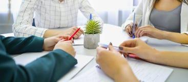 De handen van close-upjongeren met pennen en notitieboekjes op lijst stock fotografie