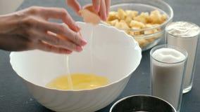 De handen van de close-upvrouw ` s breken de eieren in witte kom stock video