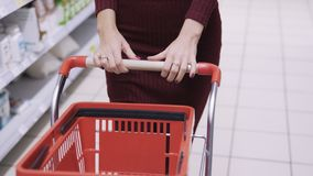 De handen van close-upvrouwen rolt rode kar in het uitwisselen van vloer van supermarkt, vooraanzicht stock video