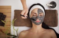 De handen van cosmetologist passen room op helft-gezicht van vrouw met cl toe Royalty-vrije Stock Afbeelding