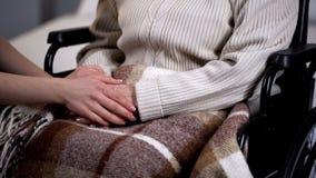 De handen van de dameholding van gehandicapt bejaard wijfje, gezinsverhoudingen, steun stock foto's