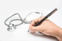 De handen van de arts met een vlak-lijst, een pen en een stethoscoop op witte lijst Stock Foto