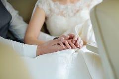 De handen van de bruidegom raken binnen de vingers van de bruid, haar palmen Royalty-vrije Stock Foto