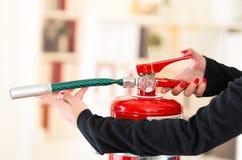 De handen van de close-upvrouw met rode nailpolish die tonen hoe te brandblusapparaat in werking te stellen stock afbeelding
