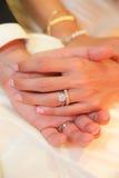 De handen van de het paarholding van de jonggehuwde Stock Foto's
