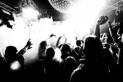 De handen van de het silhouetmenigte van de nachtclub omhoog in het stadium van de confettienstoom Stock Foto's