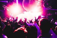 De handen van de het silhouetmenigte van de nachtclub omhoog in het stadium van de confettienstoom stock afbeeldingen