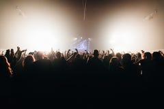 De handen van de het silhouetmenigte van de nachtclub omhoog in het stadium van de confettienstoom Royalty-vrije Stock Afbeelding