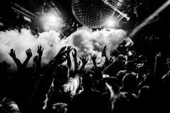 De handen van de het silhouetmenigte van de nachtclub omhoog in het stadium van de confettienstoom Royalty-vrije Stock Foto's