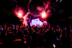De handen van de het silhouetmenigte van de nachtclub omhoog in het stadium van de confettienstoom Stock Fotografie
