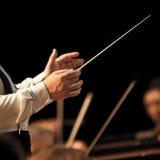 De handen van de leider op de achtergrond van het orkest stock foto's