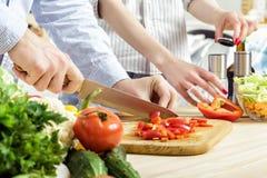 De handen van de mens hakten aan boord rode groene paprika Paar hakkende groenten in keuken Stock Afbeeldingen