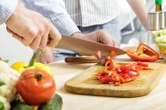 De handen van de mens hakten aan boord rode groene paprika Paar hakkende groenten in keuken Stock Foto's