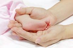 De handen van de moeder met weinig babyvoet met zorg Stock Foto