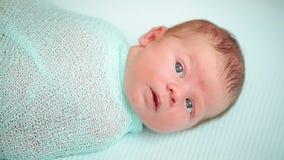De handen van de moeder wikkelen het pasgeboren baby liggen in en stock footage