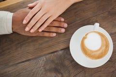 De handen van de paarholding naast cappuccino Royalty-vrije Stock Afbeelding